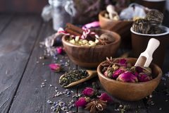 Flower and herbal tea. Different herbs for making healthy tea, cinnamon, dried rose in bowl, camomile flowers on wooden background top view, copy space Stock Photo