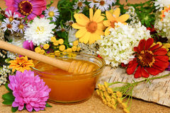 Flower honey. In a glass bowl. Among the field and garden flowers. Still life Stock Image