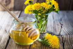 Flower honey in a glass jar and dandelions Royalty Free Stock Photo