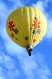 Flower Hot Air Balloon. A bright yellow hot air balloon with flowers floating high in the blue sky Royalty Free Stock Image