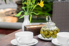 Flower and hot tea with sugar. Transparent brew glass on the table. Relax concept. Royalty Free Stock Images