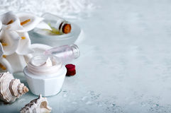 Flower and jar of moisturizing face cream for spa Stock Photos