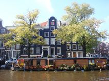 Flower laden house boat against backdrop of Amsterdam gables. Flower festooned house boat is anchored in Amsterdam canal, as traditional gabled homes form an stock photo