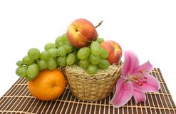 Flower of a lily. And fruit in a yellow basket on a striped brown napkin on a white background Stock Photos