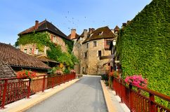 Houses of the Dordogne village of Carennac, France. Flower lined bridge in the beautiful Dordogne village of Carennac, France stock photos