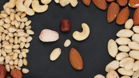 Flower made of nuts surrounded by a variety of nuts on the dark background. stock video