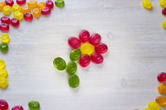 Flower made of sweet candy. On white wooden background Stock Images