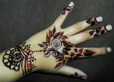Flower Mehndi designs on back of the hand. Mehndi is a form of body art originating in South Asia, in which decorative designs are created on a person`s body royalty free stock photos