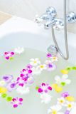 Flower and mineral water in bathtub Royalty Free Stock Images
