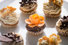 Flower mini muffins. Frosted floral mini muffins in brown, beige and orange stock image