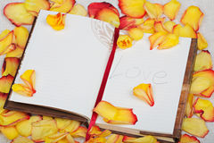 Flower with note book on roses background. Flower with note book and pen on roses background royalty free stock photography