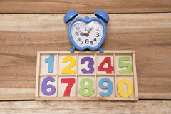 Flower numbers. Clock with wooden figures with colorful stock photography