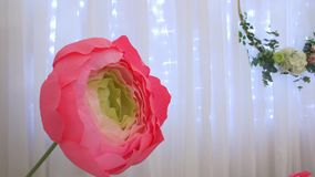 Flower paper decoration. Big corrugated paper flowers hoops rings on the white background and garland home stage design pink yellow green colors stock footage