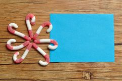 A flower pattern made out of candy canes with an empty blue note pad Stock Photos