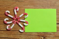 A flower pattern made out of candy canes with an empty green note pad Stock Photo