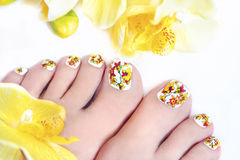 Flower pedicure. Flower pedicure with yellow orchids in the women's legs on a white background stock images