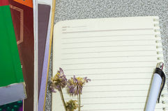 Flower pen book and a notebook on a desk Royalty Free Stock Images