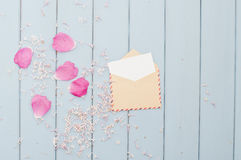 Flower petals and card in vintage postage envelope Stock Photography