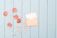 Flower petals and card in vintage postage envelope Stock Photo