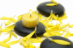 Flower petals and stones. Zen like spa with black stones with candle on yellow plants Royalty Free Stock Photo