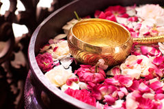 Flower petals in water with golden scoop. Use for java ceremony, like wedding, purification artifacts, etc Stock Photos