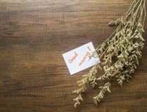 Flower and piece of paper with text 'good morning' on the wooden table close-up Royalty Free Stock Images