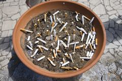 Flower planter filled full of cigarette butts Royalty Free Stock Photos