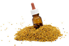 Flower pollen and medicine. Heap of flower pollen with medicine bottle in center, white background Royalty Free Stock Photography