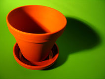 Flower Pot. An orange clay flower pot with deep shadows on a bright green background stock images