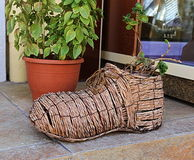 Flower pot in the shape of a boot made of rattan Stock Photo