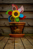Flower Pot with a toy windmill and a sunflower. Flower pot in the garden with a toy windmill and an artificial sunflower stock photography