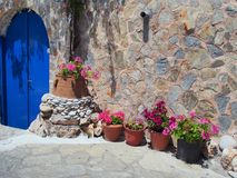 Flower Pots Outside Greek Island House. A stone walled Greek village house on Skyros, a Sporades Greek Island, with a deep blue wooden door, and many colourful royalty free stock photography