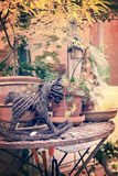 Flower pots and wooden horse ornaments on a rusty metal table in a garden in autumn Stock Photos