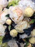 Flower power. Pile of beautiful artificial flowers, peonies, of creamy color, dozens of flowers of different color, flower show, florist industry, pack of Stock Image