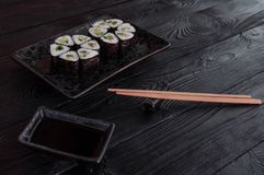 Flower from rolls maki sushi on a black stone plate. Fresh made Sushi set with cheese and cucumber. Traditional Japanese cuisine royalty free stock photo