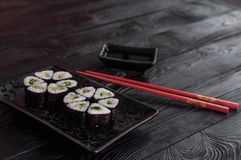 Flower from rolls maki sushi on a black stone plate. Fresh made Sushi set with cheese and cucumber. Traditional Japanese cuisine stock photography