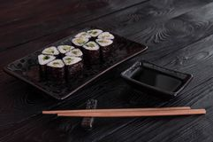 Flower from rolls maki sushi on a black stone plate. Fresh made Sushi set with cheese and cucumber. Traditional Japanese cuisine stock image