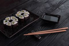 Flower from rolls maki sushi on a black stone plate. Fresh made Sushi set with cheese and cucumber. Traditional Japanese cuisine stock photo