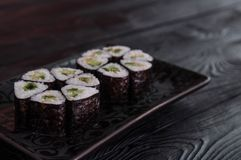 Flower from rolls maki sushi on a black stone plate. Fresh made Sushi set with cheese and cucumber. Traditional Japanese cuisine stock photos