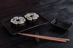 Flower from rolls maki sushi on a black stone plate. Fresh made Sushi set with cheese and cucumber. Traditional Japanese cuisine royalty free stock photography