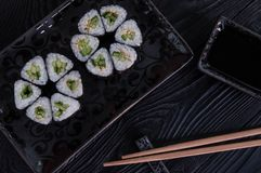 Flower from rolls maki sushi on a black stone plate. Fresh made Sushi set with cheese and cucumber. Traditional Japanese cuisine royalty free stock image