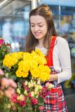Flower seller, young woman standing at shop with flower in hands. Happily looks at camera royalty free stock photo