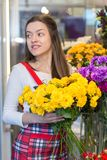 Flower seller, young woman standing at shop with flower in hands. Happily looks at camera royalty free stock photography