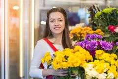 Flower seller, young woman standing at shop with flower in hands. Happily looks at camera royalty free stock images
