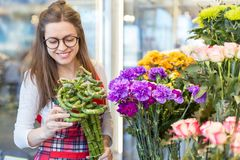 Flower seller, young woman standing at shop with flower in hands. Happily looks at camera stock photos