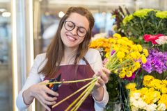 Flower seller, young woman standing at shop with flower in hands. Happily looks at camera stock image