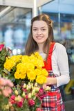 Flower seller, young woman standing at shop with flower in hands. Happily looks at camera stock photo