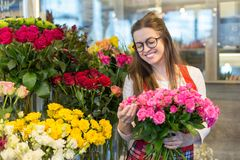 Flower seller, young woman standing at shop with flower in hands. Happily looks at camera stock photography