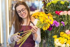 Flower seller, young woman standing at shop with flower in hands. Happily looks at camera royalty free stock image
