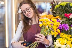 Flower seller, young woman standing at shop with flower in hands. Happily looks at camera stock images